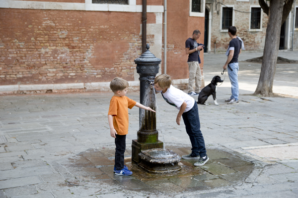 The boys drinking from the fountain.