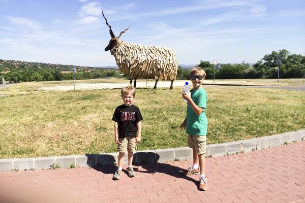 The boys posing next to the sculpture outside of Skanzen.