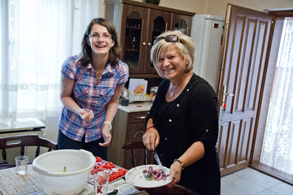 Rita and Agi slice vegetables.