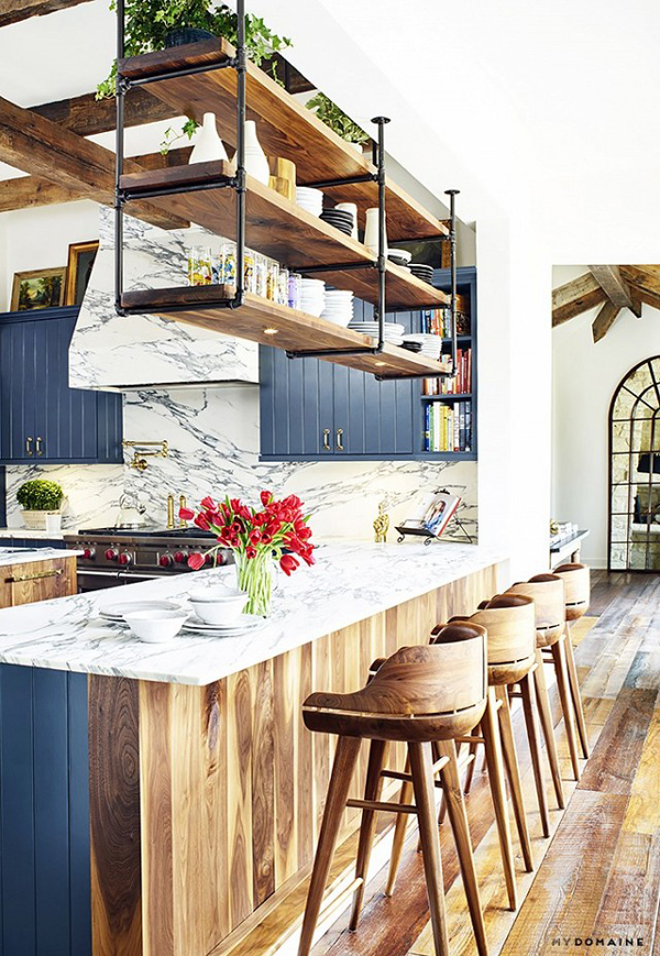 The masculinity of the open hanging shelves, balances the feminine touches in the rest of the kitchen.